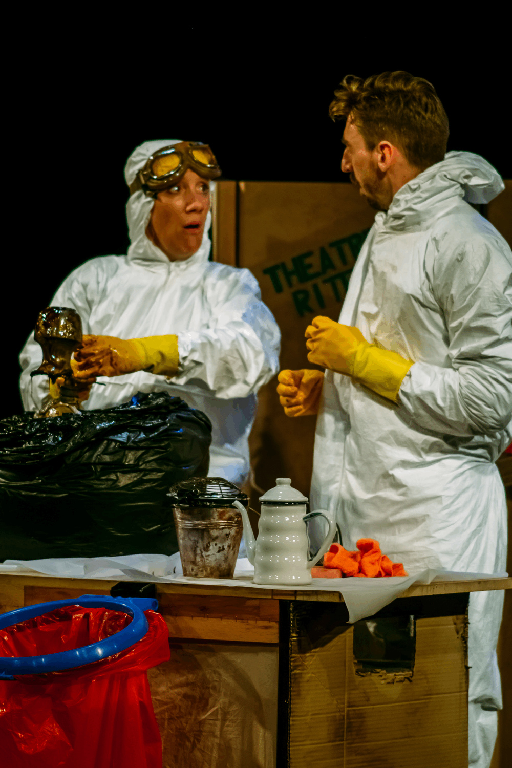 two puppeteers in chemical cleaning suits, wearing rubber gloves lift a duck puppet out of a bin bag