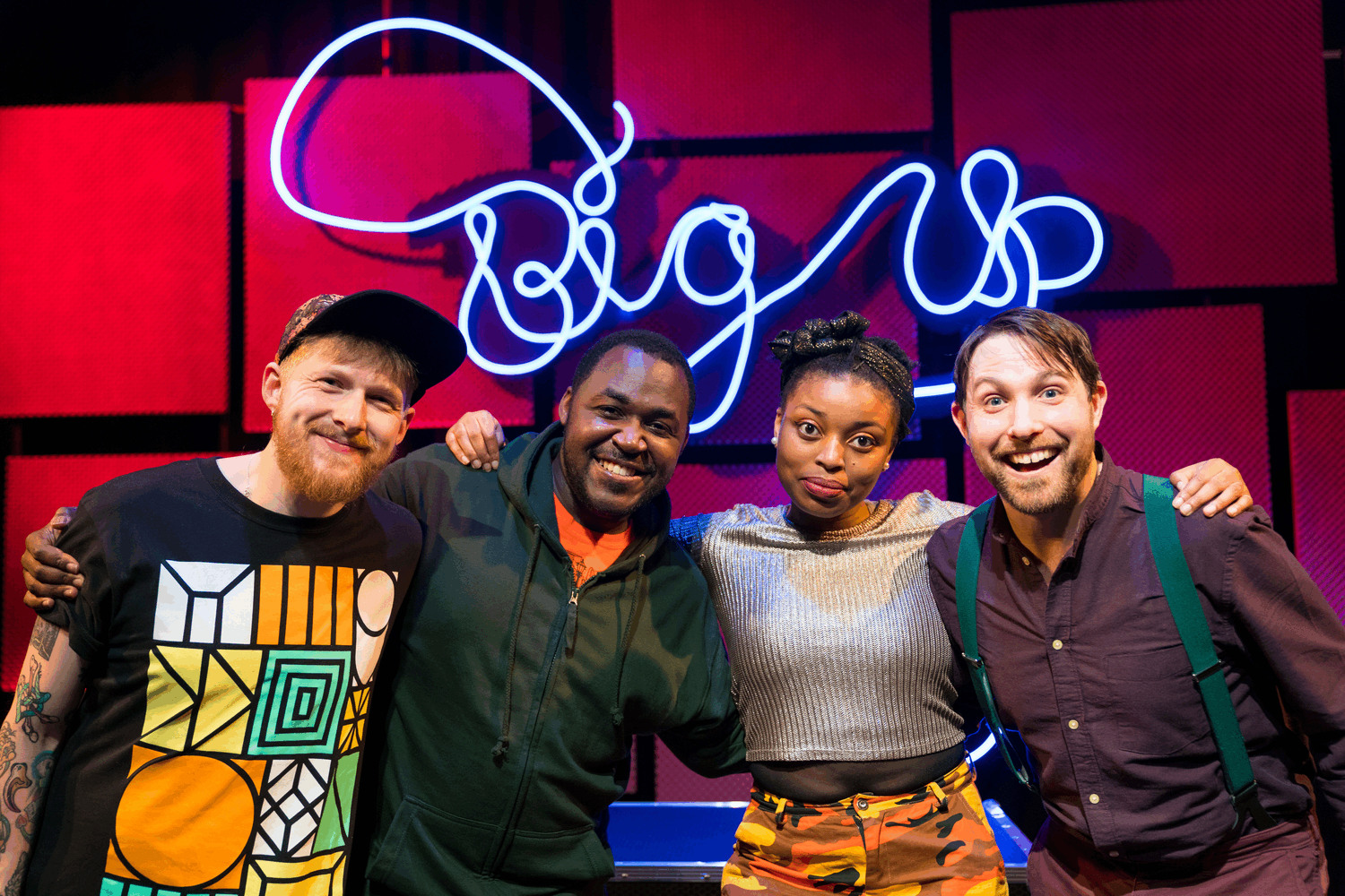 Cast: Jack Hobbs, Clarke Edwards, Dorcas Sebuyange, Iestyn Evans, wearing colourful clothing and posing with arms around one another in front of blue neon sign reading Big Up!
