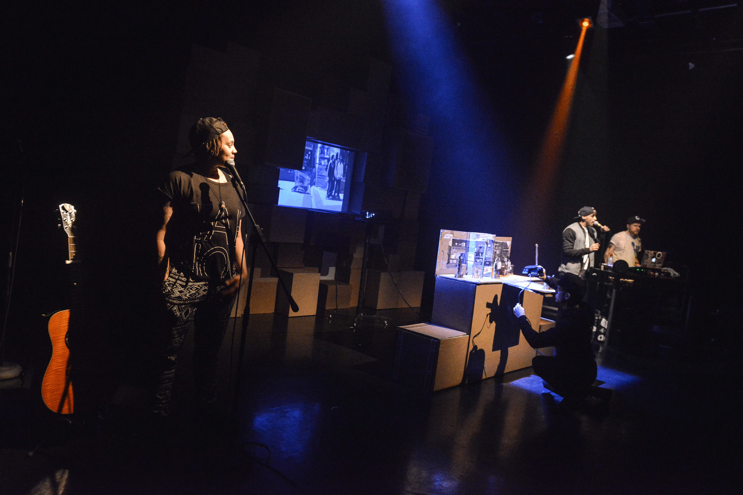Three performers stand on stage at mics in a gig setting. there are cardboard boxes in the background and atmospheric lighting