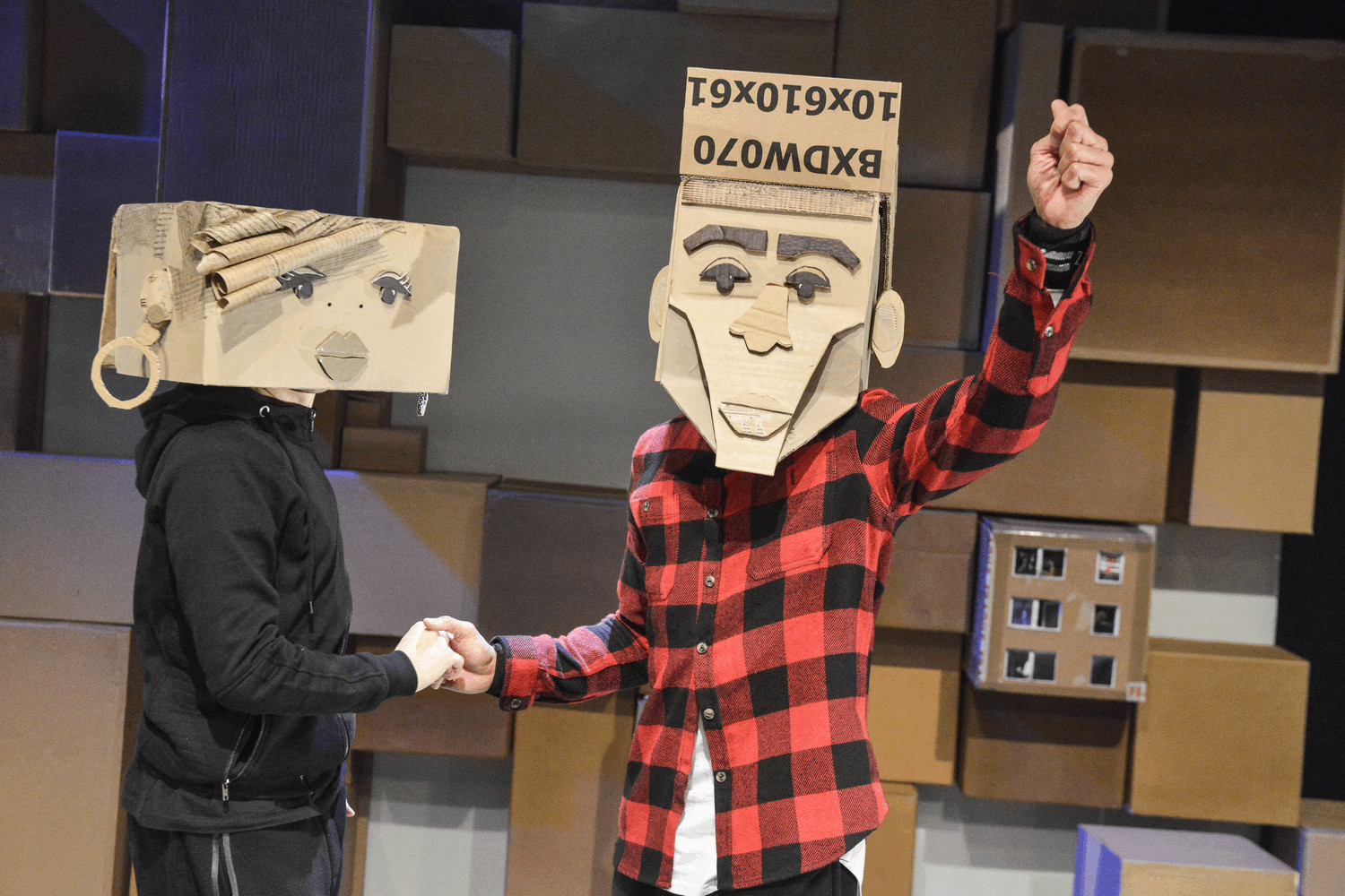 Two people have boxes on their heads created to look like faces. They are holding hands