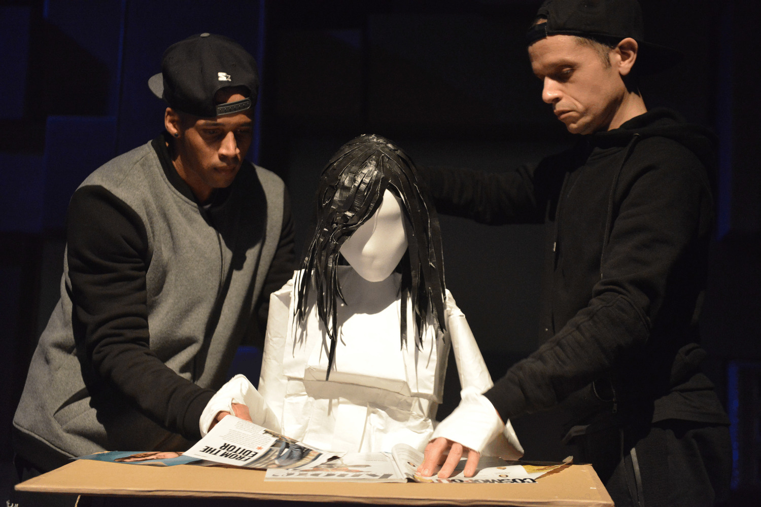 Two puppeteers manipulate a female puppet reading magazines. She is made of white paper and her hair is black.