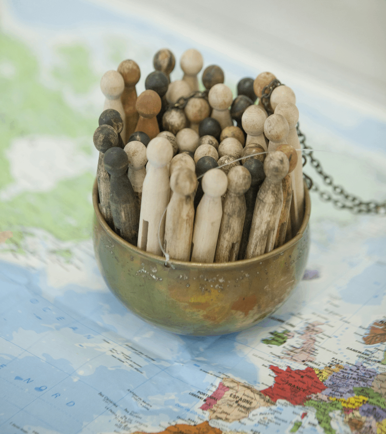 different coloured pegs tightly packed in a metal bowl sitting on a map