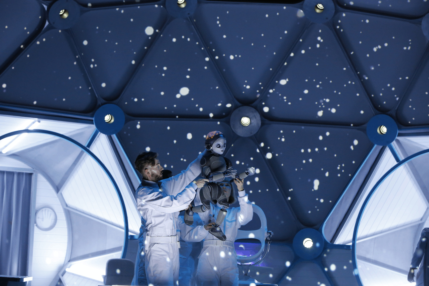 stars appear moving across the inside of a sci fi laboratory whilst lab assistants hold robot boy in the air
