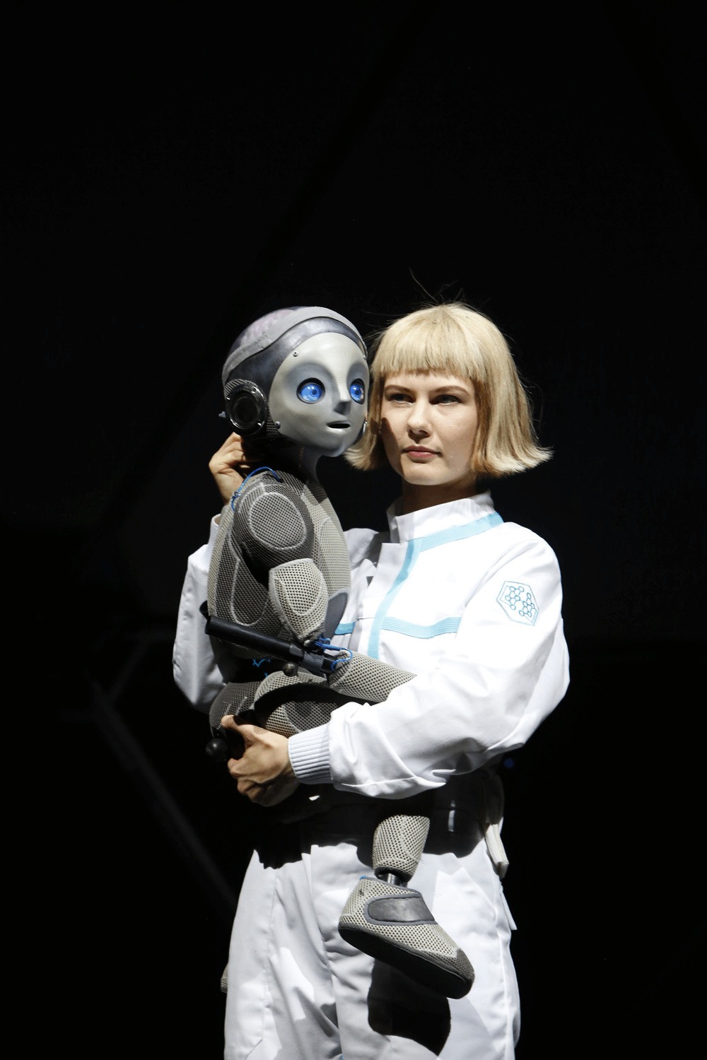 close up of Robot Boy being held tightly by a Lab assistant dressed in sci fi white ovearalls