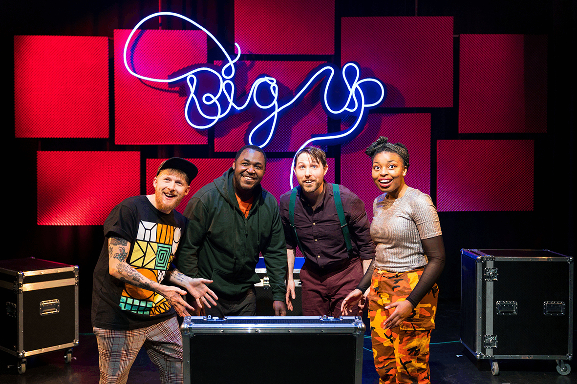 beatboxer, two puppeteers and a singer standing infront of a neon blue Big Up sign
