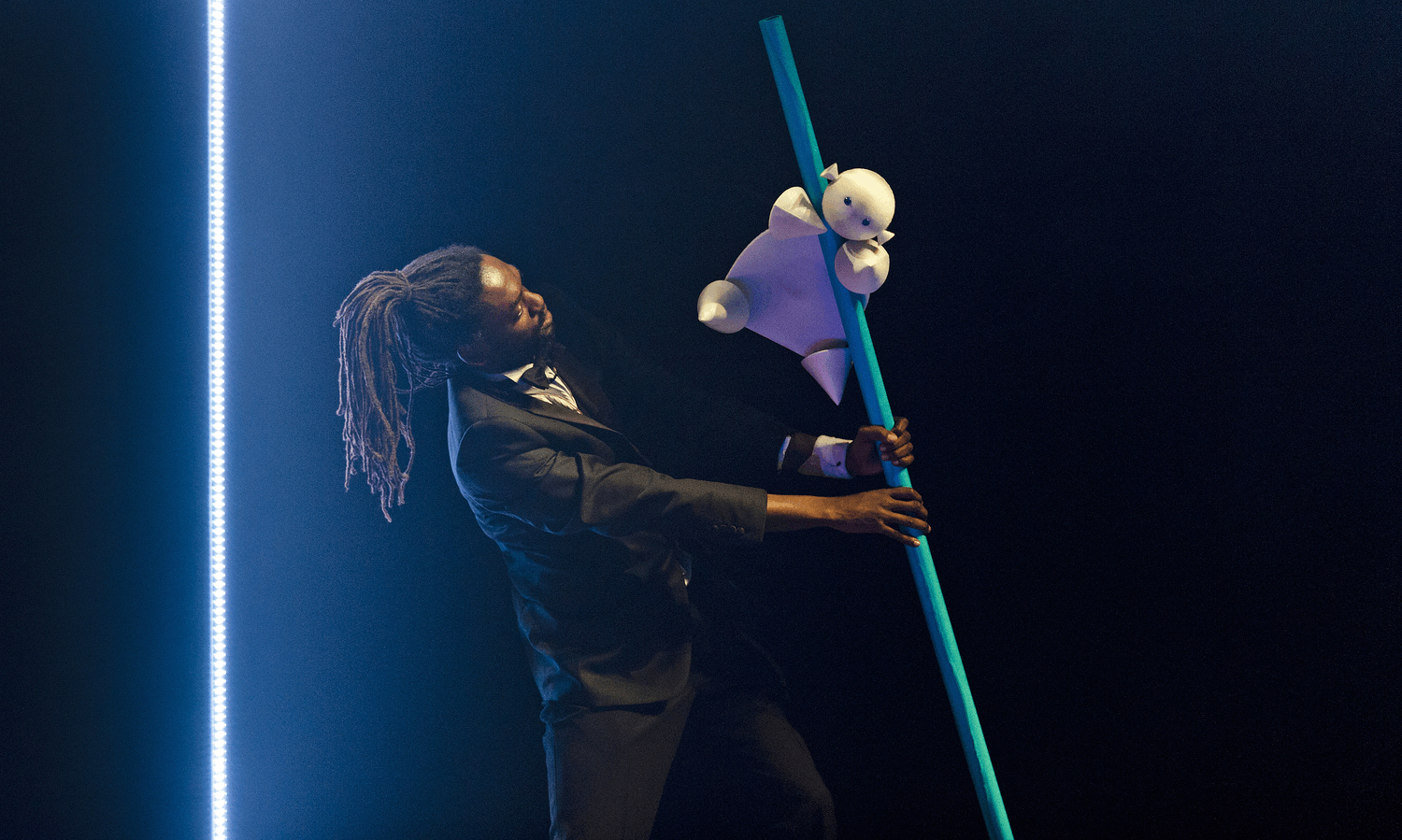 A performer with dreadlocks holds a blue pole at an angle as a tiny white puppet baby slides down it