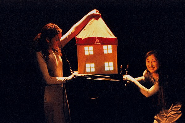 Two women performers hold up a small house made of fabric between them. One of them women is holding the house up by the top of its roof. The house is orange and it has four window
