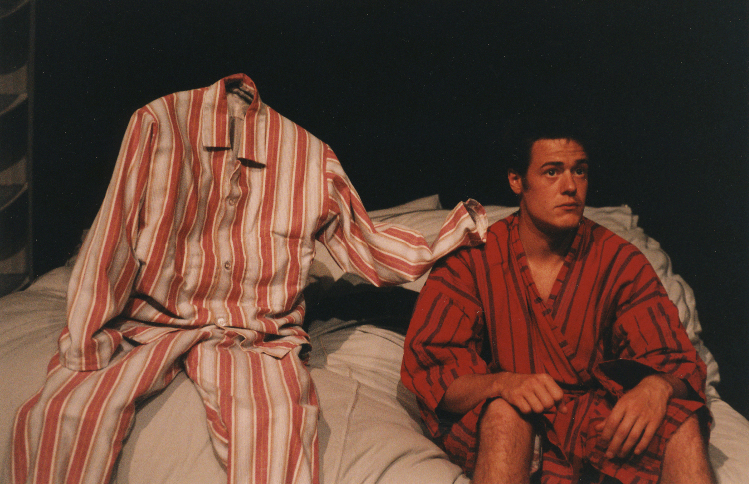 a puppet made out of pyjamas sits with his hand on the shoulder of a man in a dressing gown