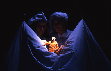 A tiny puppet man in red pyjamas is cradled in a pillow and watched by two people wearing pyjamas and nightcaps. From the touring show Sleep Tight.