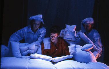A man in pyjamas sits in bed reading a book, as two puppets made out of pillows lie next to him, manipulated by two people in pyjamas