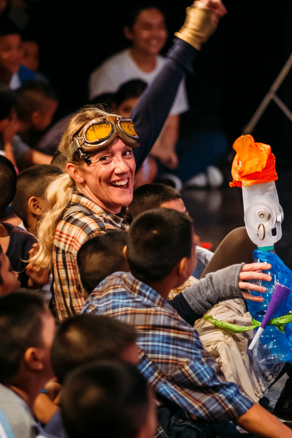 performer sitting with audience of young children, holding puppet made of plastic bags and plastic milk bottle