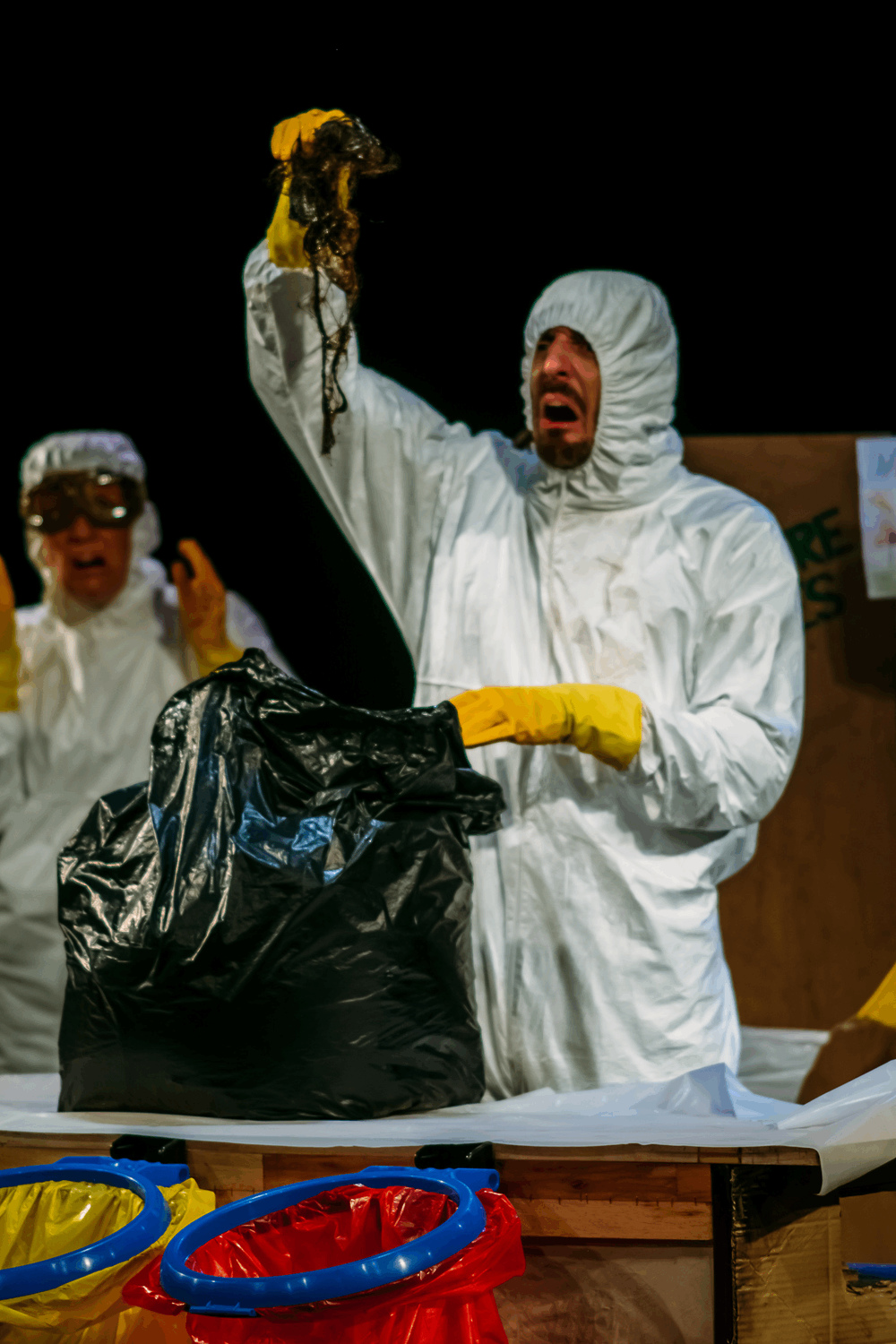 performer in white hazard suit lifts hair covered in oil out of a bin bag