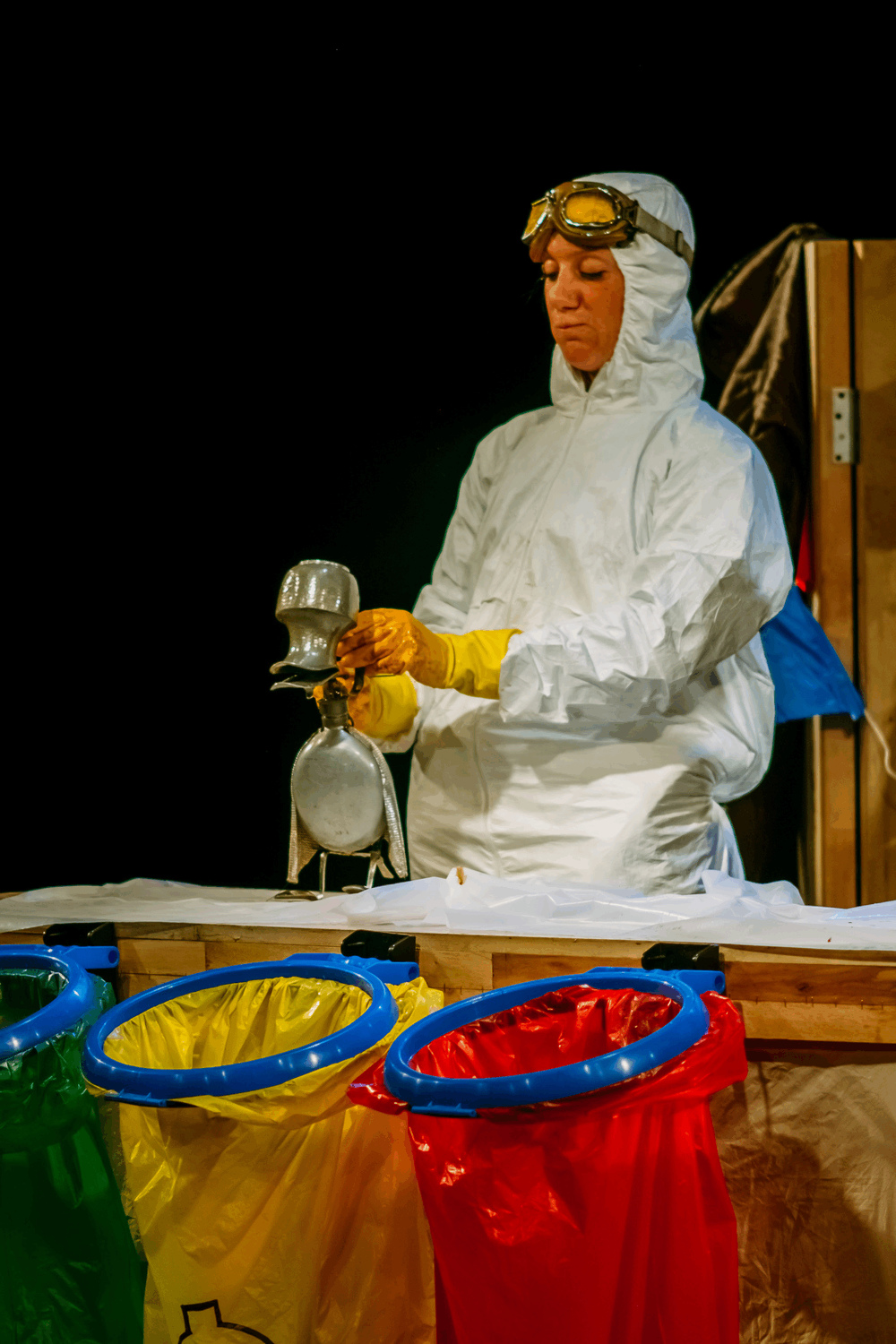 Performer in white hazard suit, goggles and yellow gloves animates a duck made out of a tea pot, jug and spoons