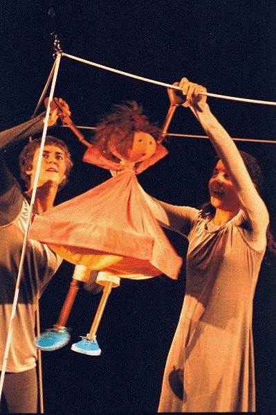 A puppet girl swings from a rope