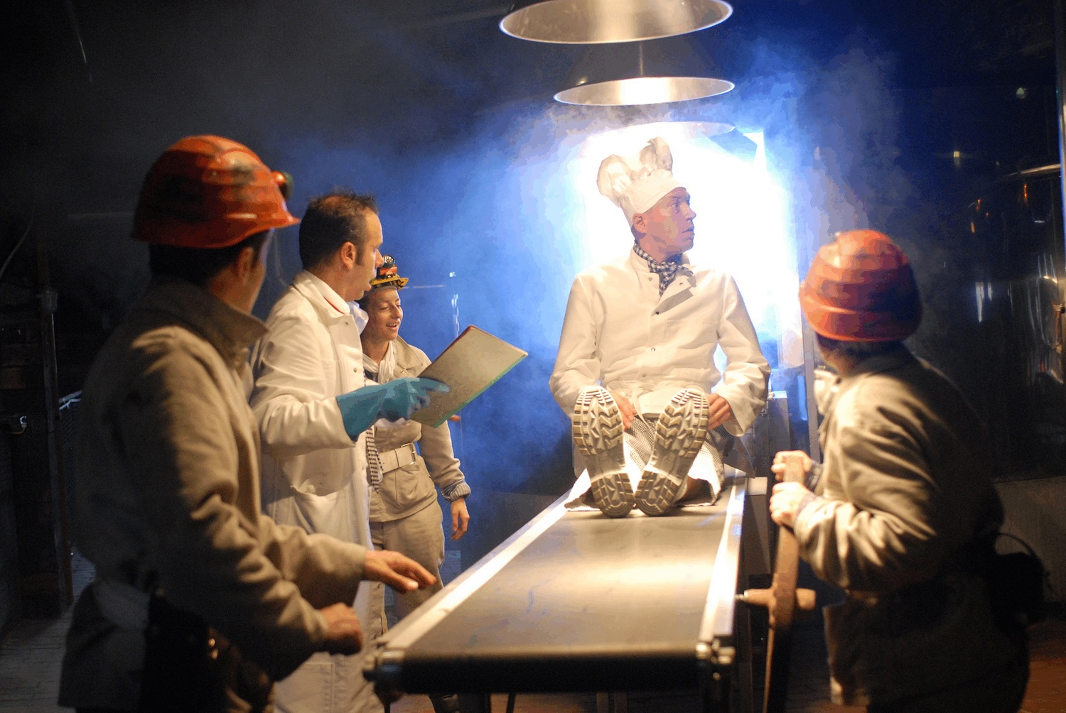 A man wearing a chef's outfit and hat sits on a conveyer belt as 4 performers in different iconic white suits watch on