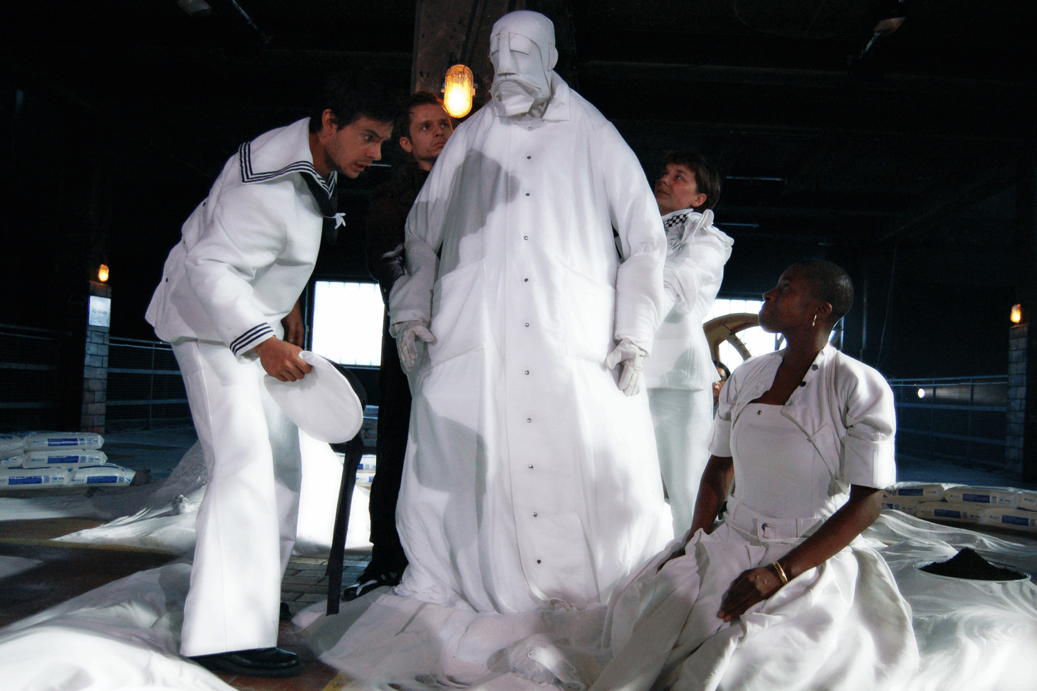 a 7 foot tall white coated puppet, with a beautiful face made out of fabric, is surrounded by performers sitting in salt