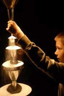 a young boy holds the bottom of a nossle to slowly pour salt over a a series of stacking cones creating a waterfall