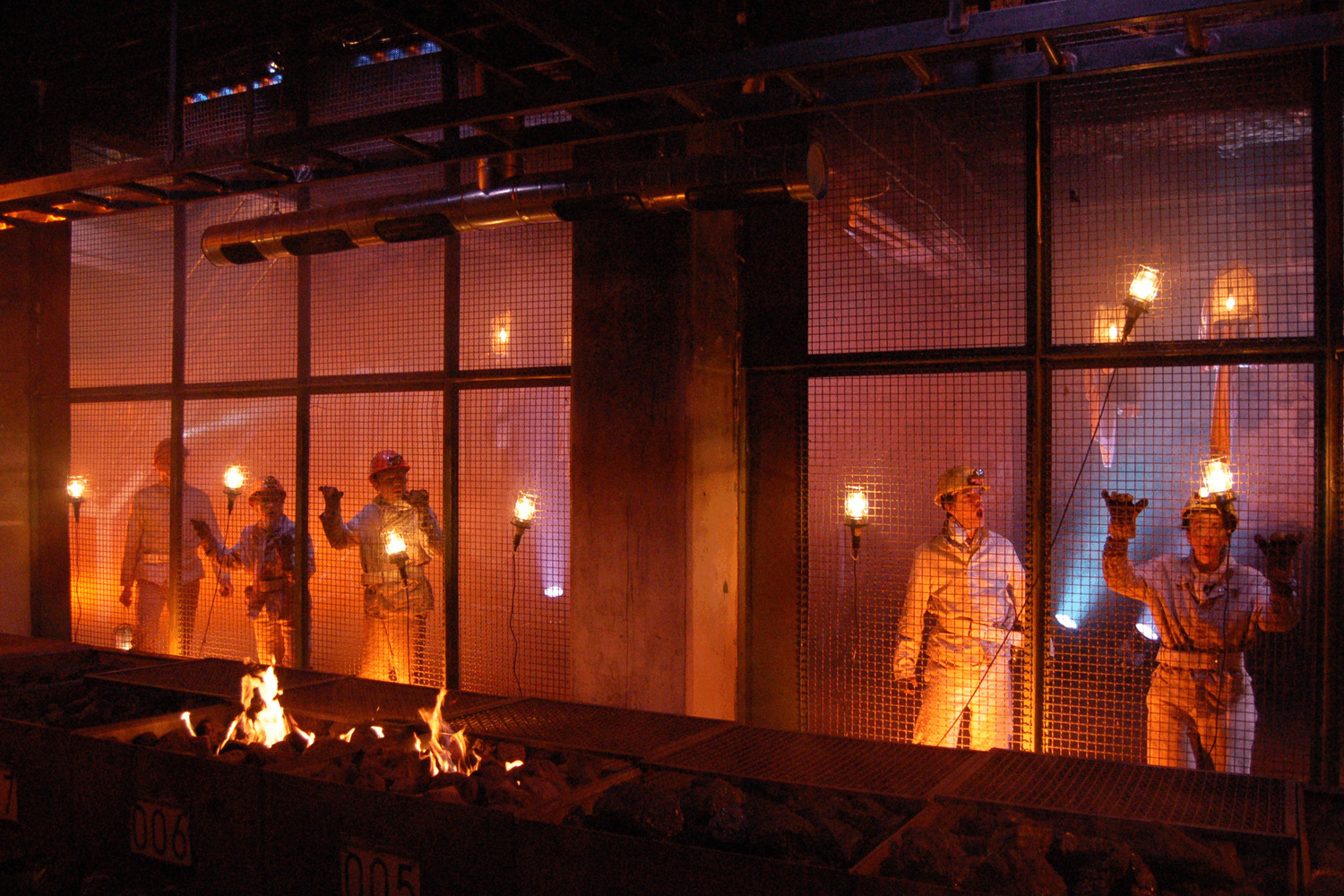 5 performers dressed as miners stand behind a meshed wall looking at a furnace full of fire