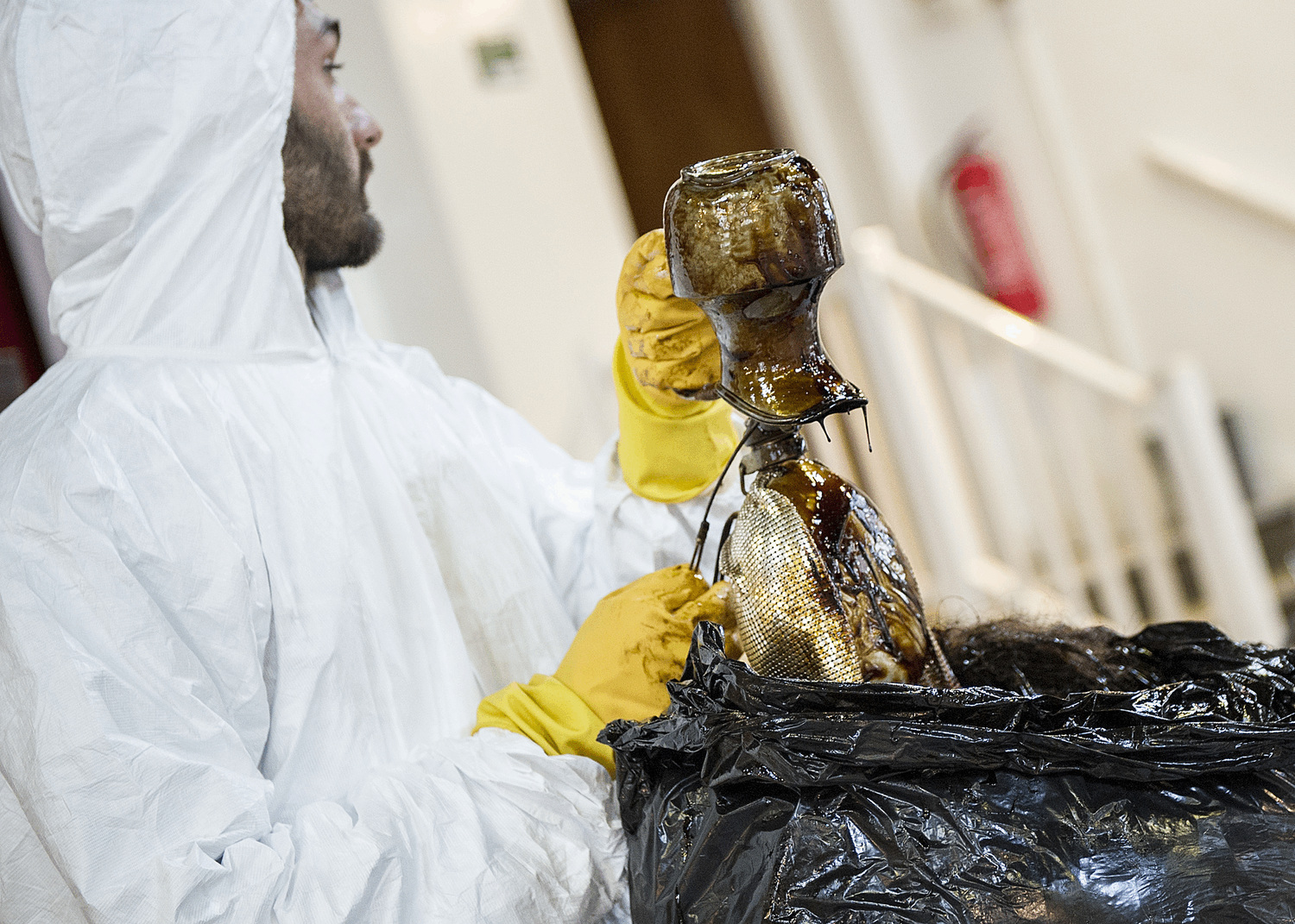 A man in a white hooded hygene suit and yellow gloves, lifts a mucky duck out of a bin bag.  The duck is made of a silver tea set