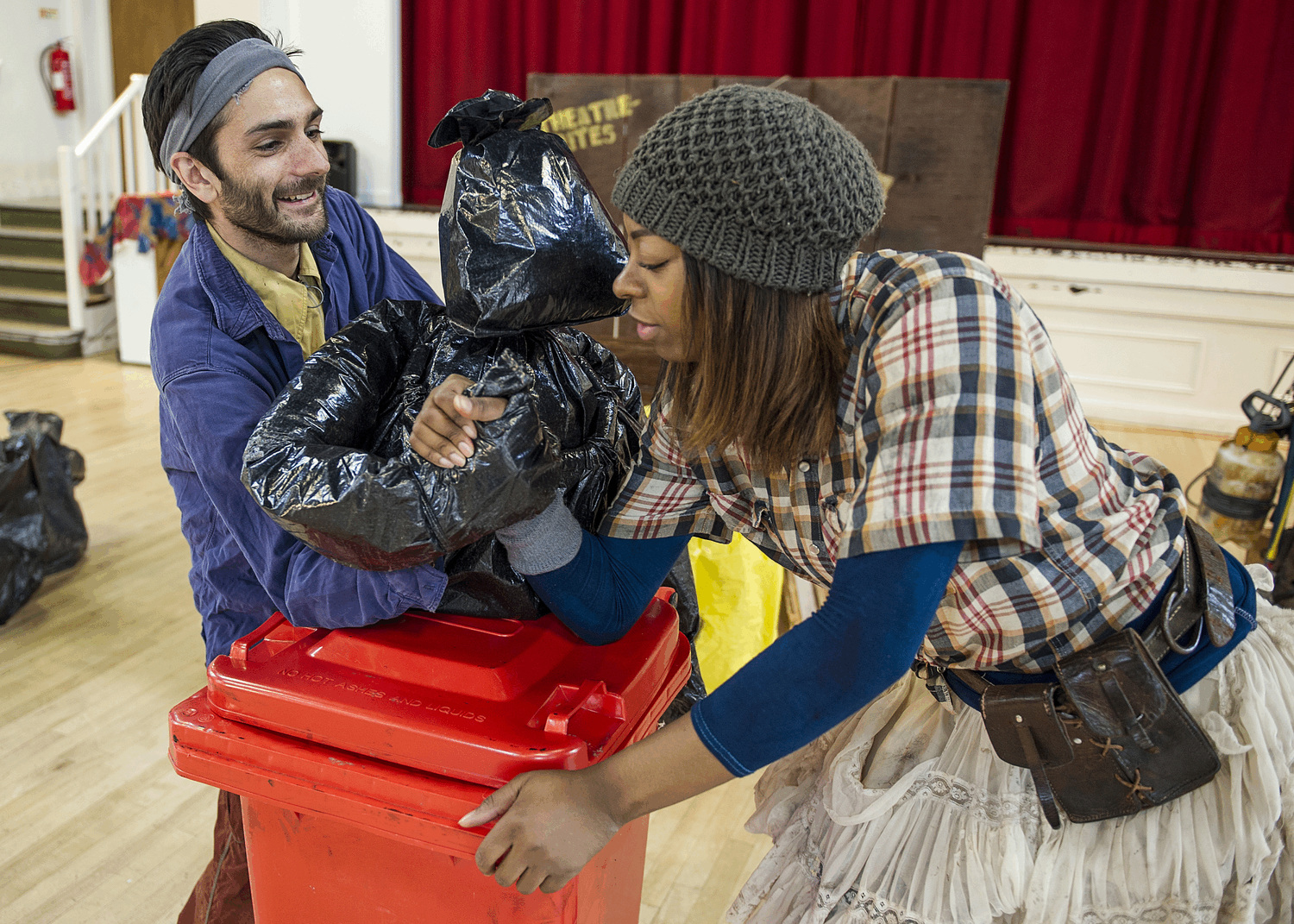 a woman arm wrestles with a puppet made of bin bags.  The puppet is manipulated by a puppeteer and is sitting on top of a wheelie bin