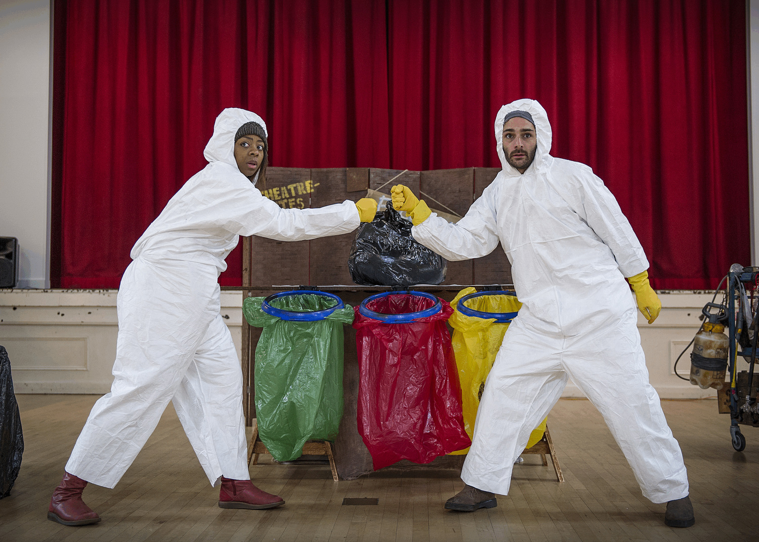 Two people wearing white hygenie suits and yellow gloves, fist bump each other as they stand in front of 3 different coloured recycling bags