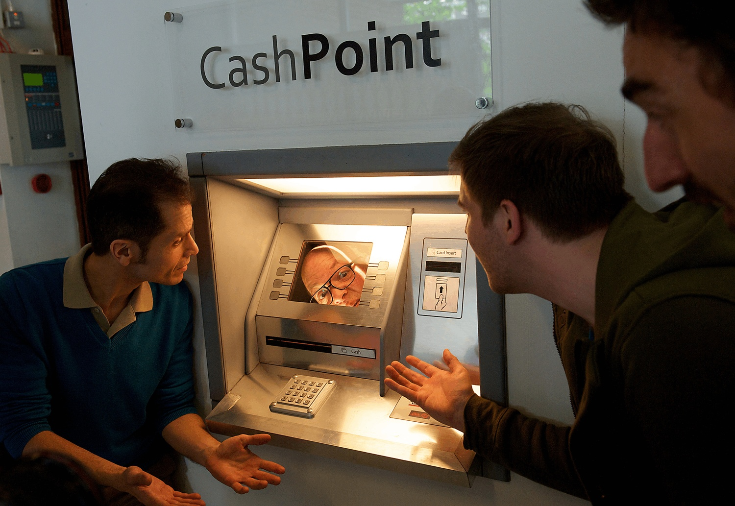 A man's face appears from inside a cash point, as 3 people look on.