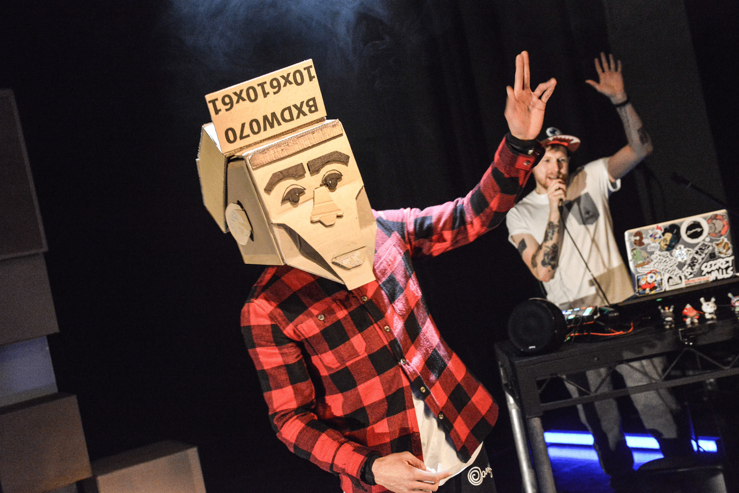 A man stands with his hand in the air. He is wearing a cardboard box with a face on it. In the background another man stands with his hand also in the air. He is beatboxing