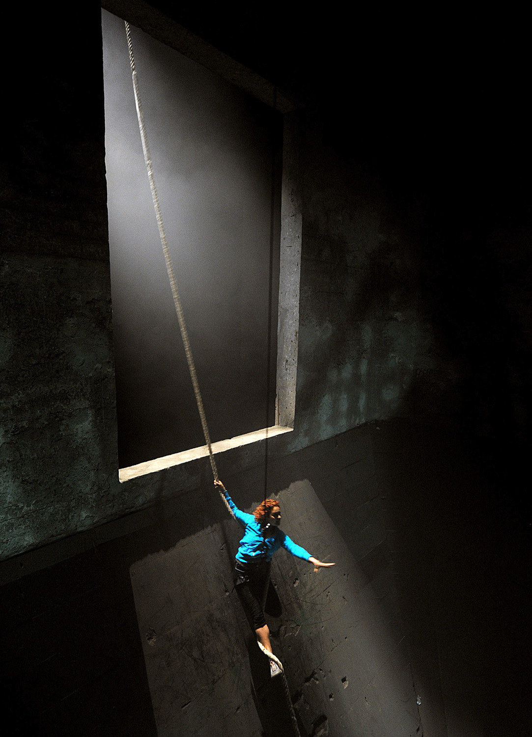 woman dangles from a rope in a hanging from the top of a long concrete shute, trying to find a way into paradise