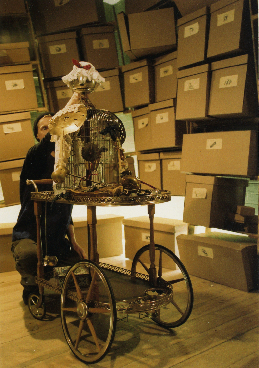In a room piled high with staggered brown boxes a man manipulates the puppet of an old woman made out of a bird cage, a tea trolley and silver teapot with a crocheted hat.  From th