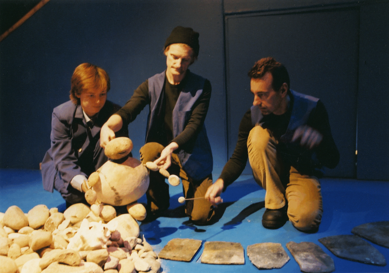 Two puppeteers and a woman museum guide manipulate a pebble puppet to climb out of a pile of puppets and walk a long a path made of stone.  From the site-specific show Finders Keep