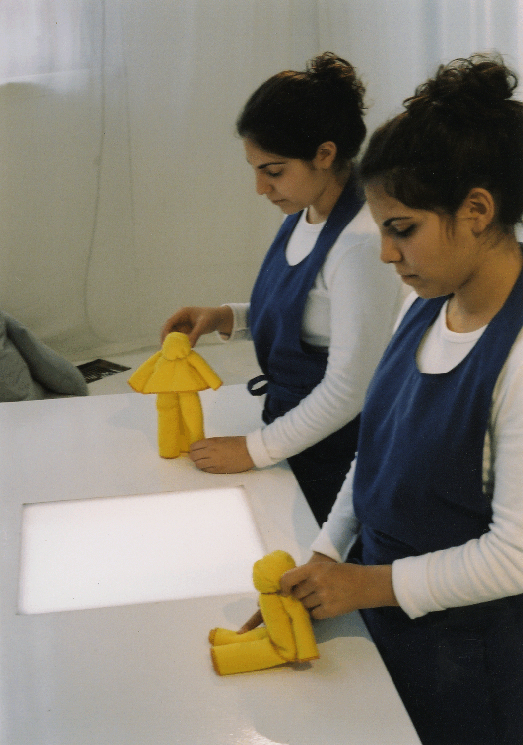 Twin girls in aprons make dolls out of yellow dusters from the site-specific show Finders Keepers