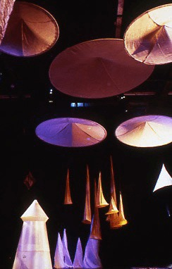 Large fabric cones are suspended from the ceiling, almost touching fabric cones sitting on the floor