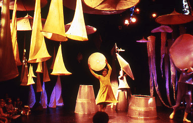 large cones hang from the ceiling and underneath two woman hold circular and triangluar shapes in the air as they move around cones on the floor