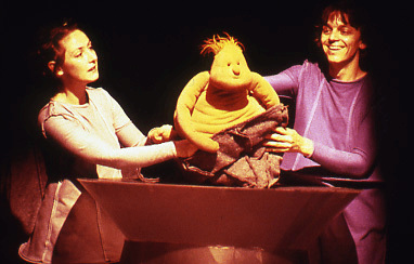 a rotund puppet with a chubby oval face and a smattering of ginger heir appears out of a conical bag, held by two puppeteers