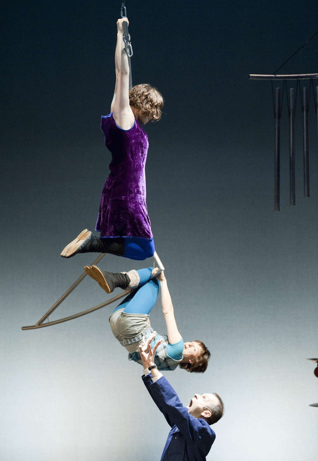 a man holds on to an aerialist's back as she hangs from a triangle and above her another aerialists hangs from a higher triangle