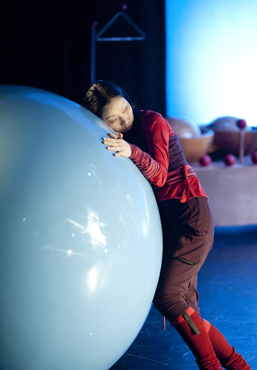 percussionist Nao Masuda hugs a gigantic ball, which is bigger than she is
