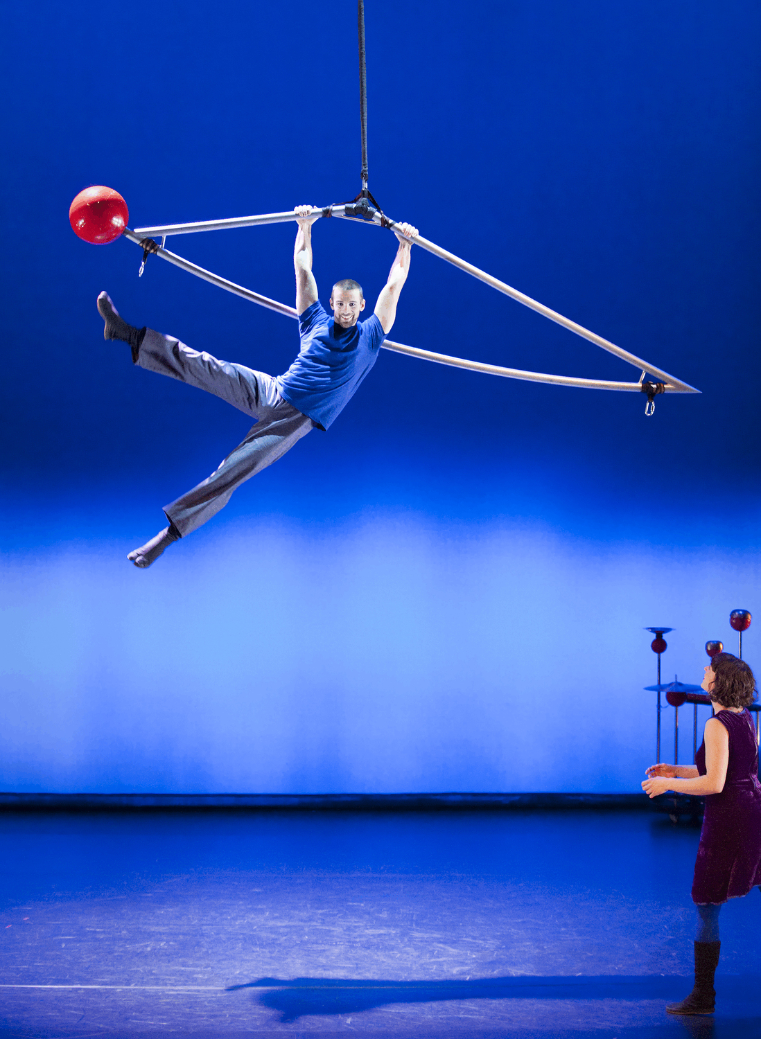 a aerialist hangs for a triangular metal shape with a red ball ot one end high above the stage. Another female performer watches from below