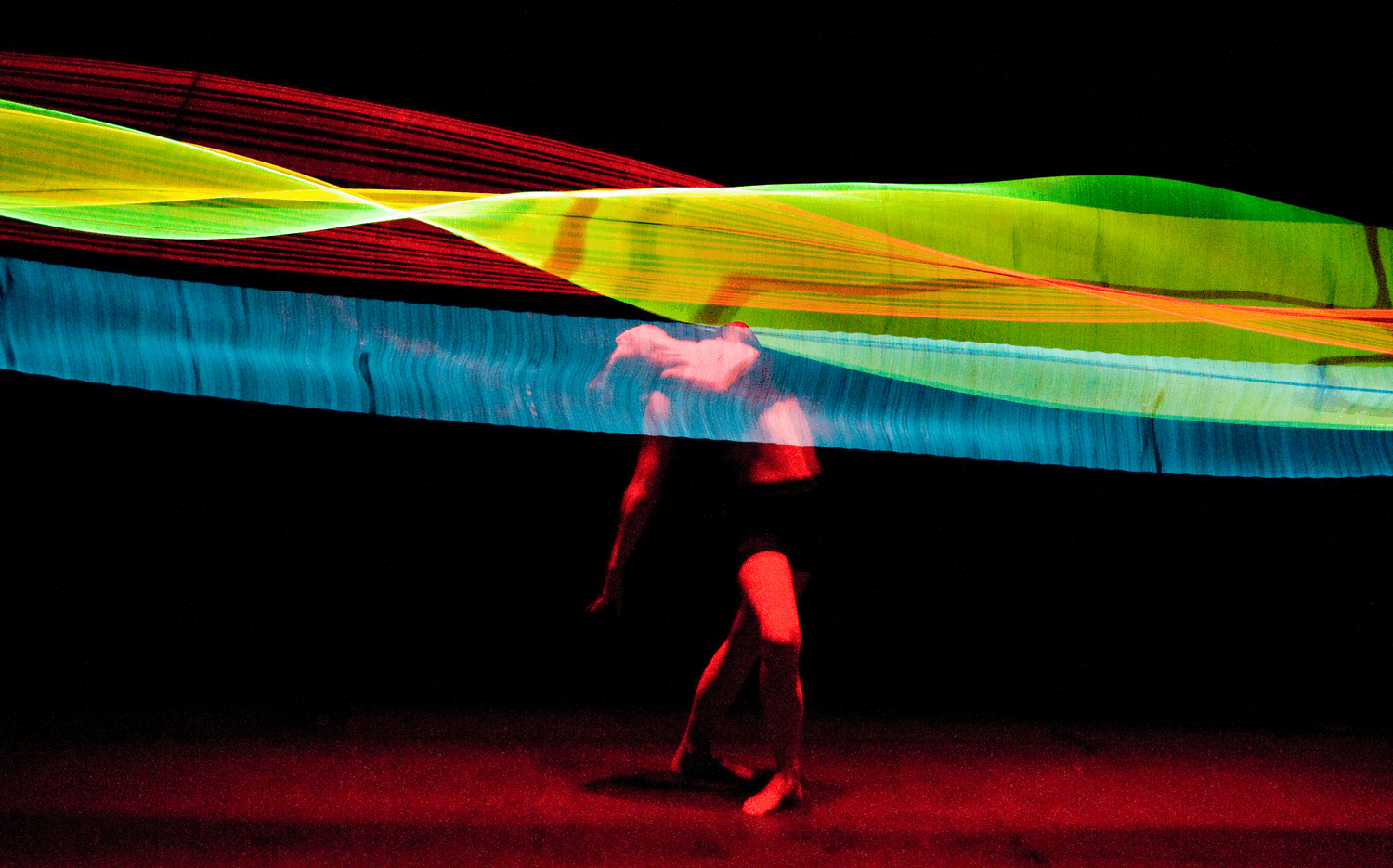 dancer moves through silk cloths being stretched across the stage