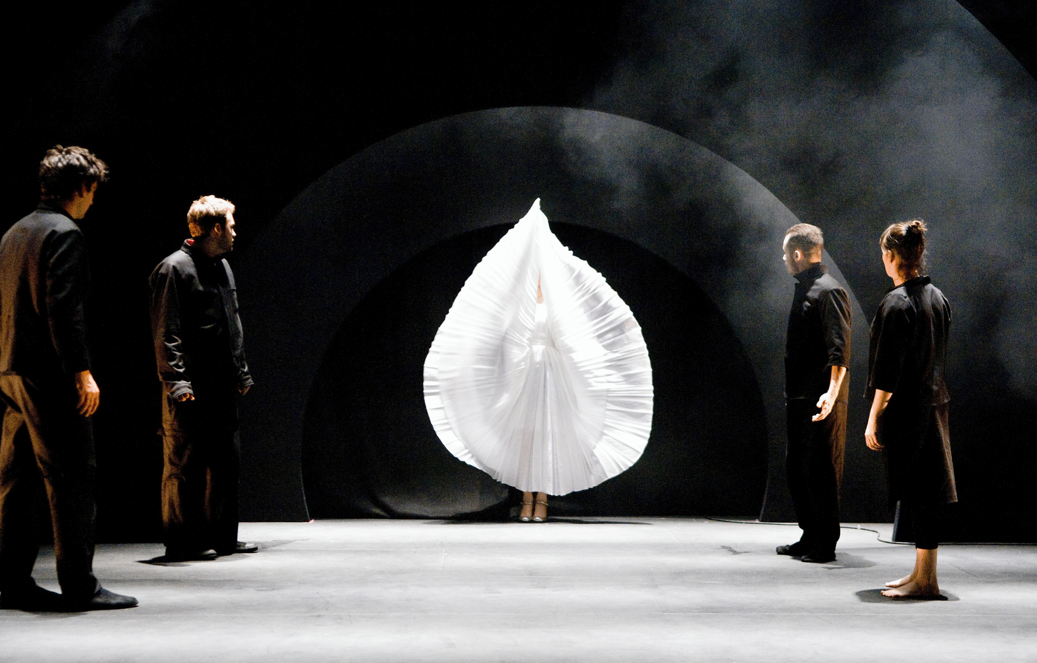 in the middle is a petal shape created out of fanning a pleated dress above a dancer's head.  4 performers watch the petal