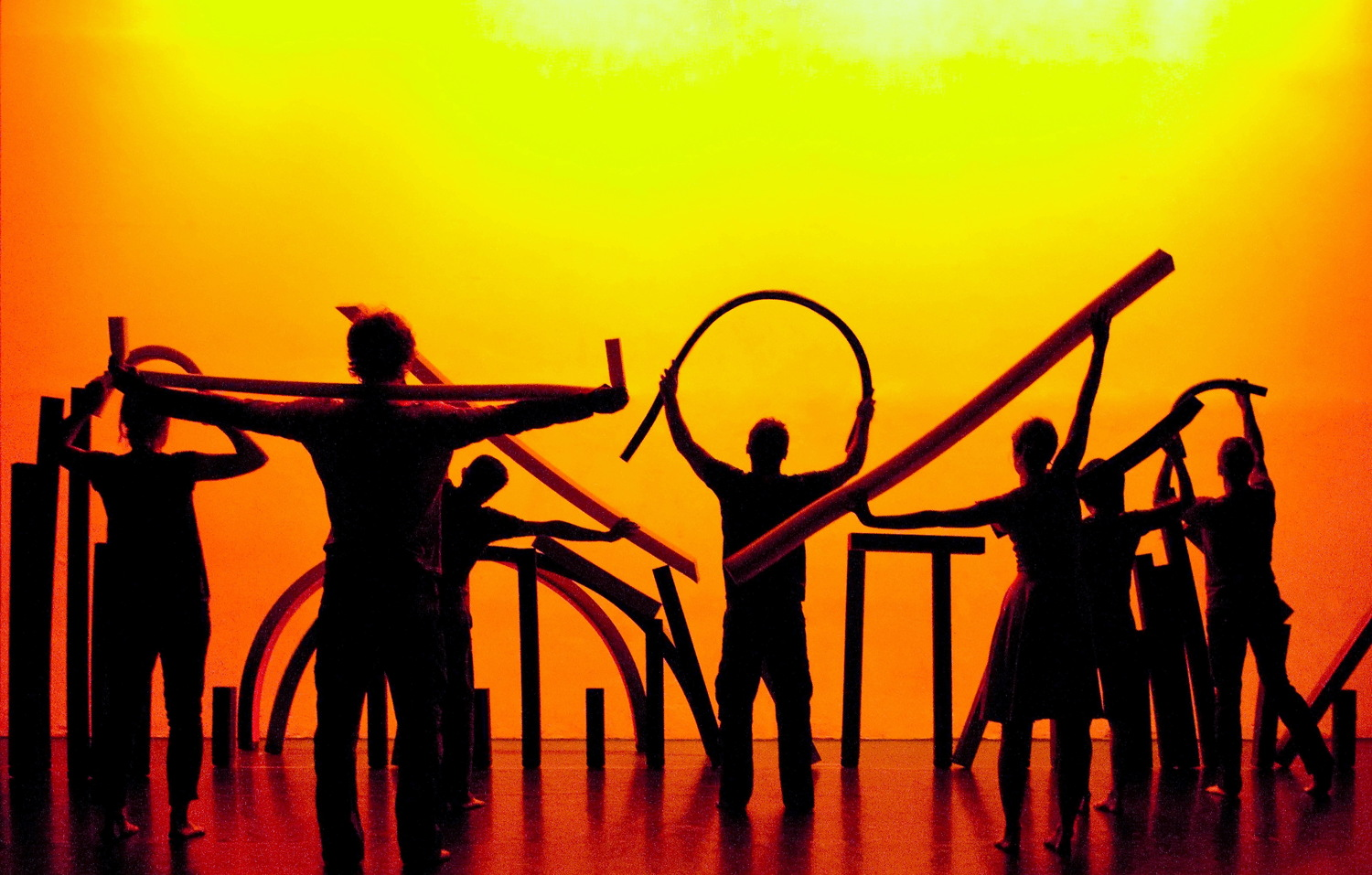A abstract cityscape is created by performers, with backs to audience, holding different shaped foam lines in a mutlitude of positions against yellow and orange backdrop