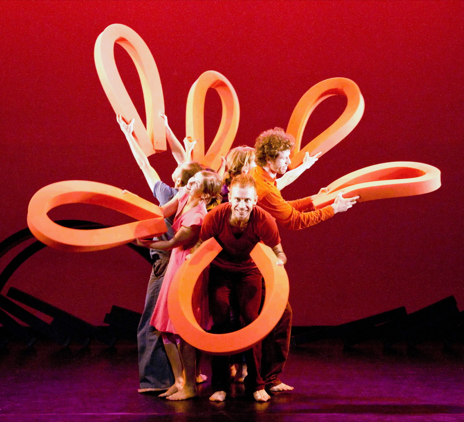 a group of dancers huddled in a circle, each hold out a semi a horseshoe shaped line of foam, creating the illusion of a flower with its petals