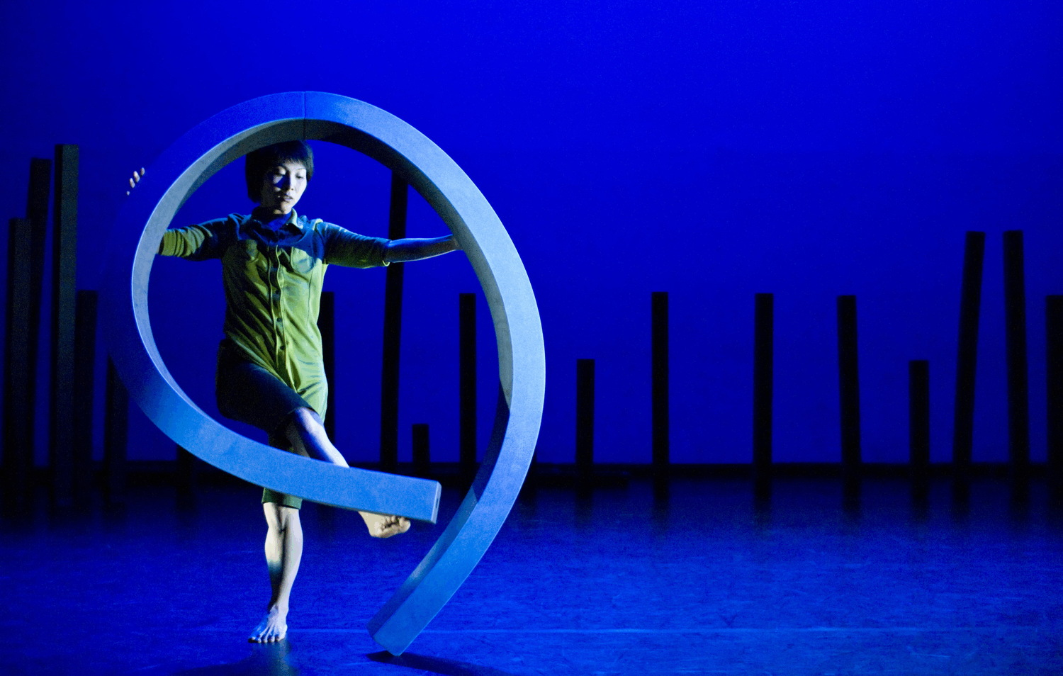A dancer bends a long blue foam line into a beautiful shape, tilting one end up with her pointed foot against a blue backdrop