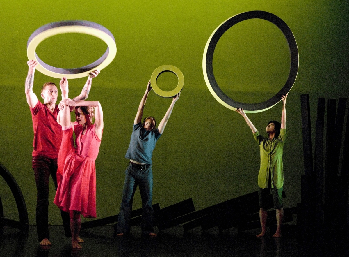 3 dancers hold large circles in the air, as one dancer lifts her leg to her head.