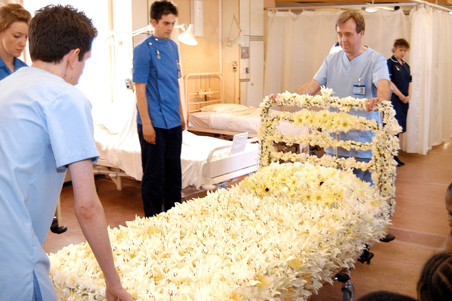 a hospital bed covered in flowers is wheeled through a ward