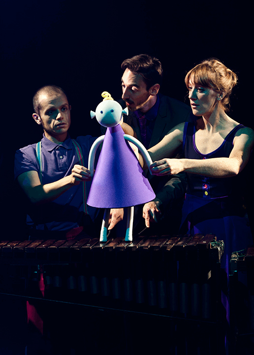 a conical shaped puppet girl stands on a xylophone as 3 puppeteers operate her and her feet play a tune.