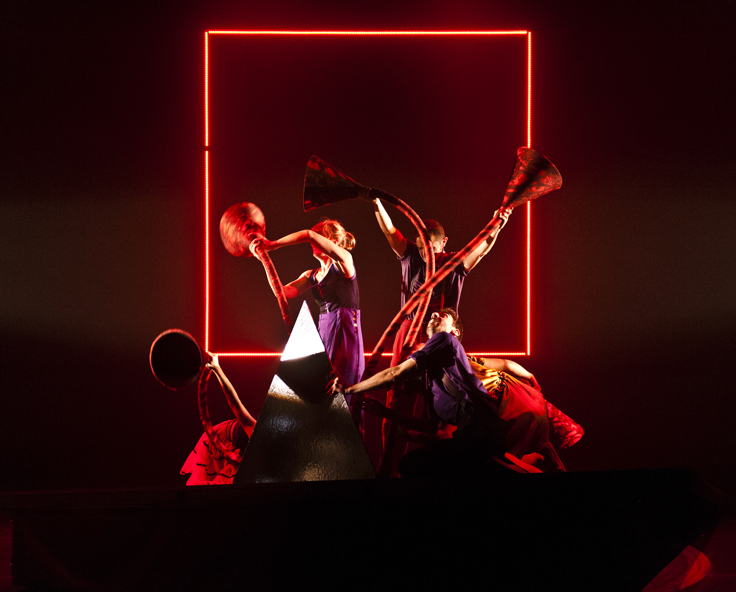 Framed by a red light, a group of performers wrestle with giant red tentacles made out of foam cones