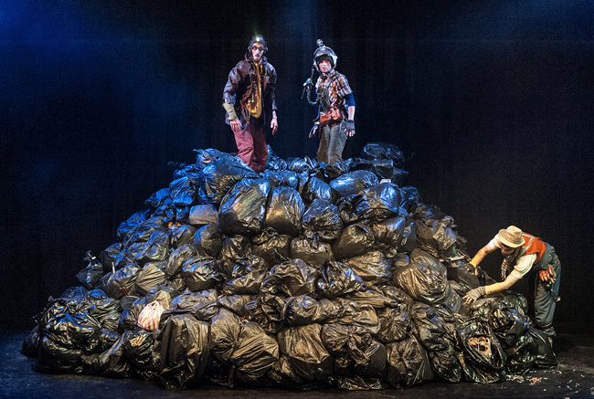 Two men dressed as excavators with old fashioned helmets stand on top of a mountain of bing bags, as another man searches through the bags below.