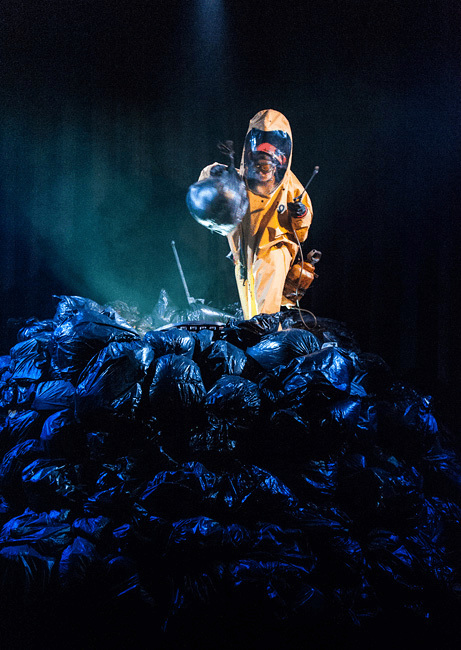 A woman dressed a large yellow biohazard suit stands on top of a huge pile of rubbish bags