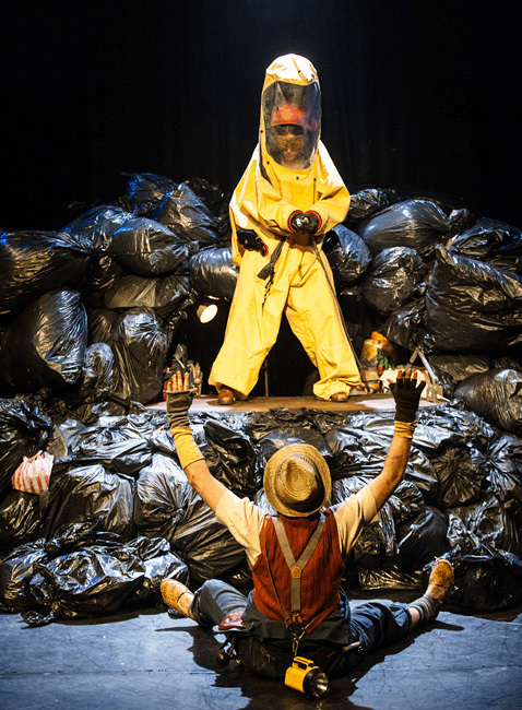 Woman in biohazard suit stands in the middle of a pile of bin bags and sprays a man sitting with his hands up on the floor below