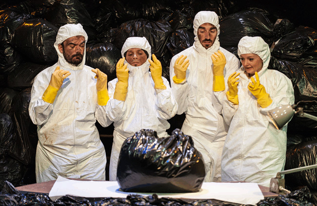 4 performers wearing white hooded hygene suits, hold their yellow gloved hands in the air as they prepare to open a full bin bag